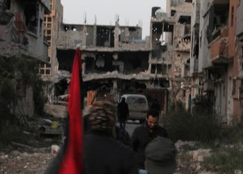 In this picture taken Tuesday, Feb. 23, 2016, a civilian fighter, holding the Libyan flag, walks in front of damaged buildings in Benghazi, Libya. Army units, backed by civilian fighters, cleared a major part of the eastern city of Islamic extremists Tuesday, following nearly two years of deadly fighting. (AP Photo/Mohammed el-Shaiky)