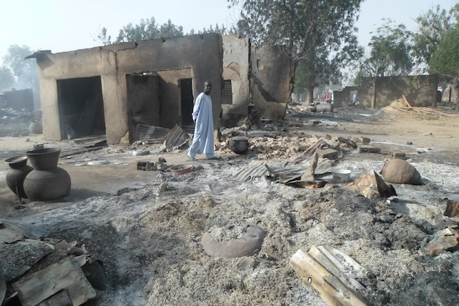 A man walks past burnt out houses following an attack by Boko Haram in Dalori village 5 kilometers (3 miles) from Maiduguri, Nigeria, Sunday Jan. 31, 2016. A survivor hidden in a tree says he watched Boko Haram extremists firebomb huts and listened to the screams of children among people burned to death in the latest attack by Nigeriaí s homegrown Islamic extremists. (AP Photo/Jossy Ola)