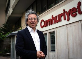 Can Dundar, the editor-in-chief of opposition newspaper Cumhuriyet, speaks to the media outside the headquarters of his paper in Istanbul, Turkey, Thursday, Nov. 26, 2015. Turkey's Anadolu state-run news agency says a prosecutor has demanded that Dundar be jailed on charges of terror propaganda and for revealing state secrets, when the Cumhuriyet paper published what it said were images of Turkish trucks carrying ammunition to Syrian militants. (ANSA/AP Photo/Vedat Arik, Cumhuriyet)
