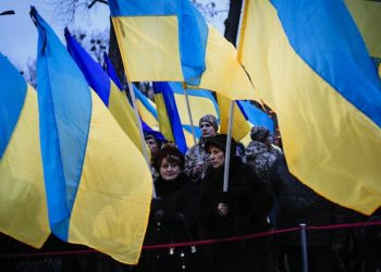epa05046193 Ukrainians hold their National flag during a memorial ceremony near a monument to the victims of the Great Famine in Kiev, Ukraine, 28 November 2015. Ukrainians light candles to mark a day of memory for the victims of the Holodomor in 1932-1933. The Holodomor was a man-made famine provoked by Soviet dictator Josef Stalin. The result was the death to more than five million Ukrainians.  EPA/ROMAN PILIPEY