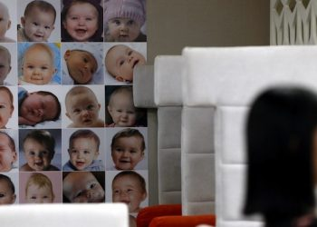 epa04360807 A woman waits for an advisor next to portraits of babies at a fertility clinic in Bangkok, Thailand, 20 August 2014. Thailand has re-examined its surrogacy laws following the scandal of a surrogate baby affected with Down syndrome being rejected by an Australian couple, which took his twin sister only, and the case of a 24-year-old Japanese man who is suspected of fathering at least nine surrogate babies. Authorities have been examining surrogacy clinics and practices around the country, but complain that legal loopholes make cases difficult to investigate.  EPA/RUNGROJ YONGRIT