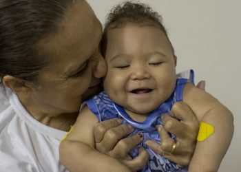 Caio Julio Vasconcelos who was born with microcephaly is kissed by a therapist at the Institute for the Blind in Joao Pessoa, Brazil, Thursday, Feb. 25, 2016. Researchers from the Centers of Disease Control and Prevention continue to fan out across one of Brazil's poorest states in search of mothers and infants for a study aimed at determining whether the Zika virus is causing babies to be born with unusually small heads. (AP Photo/Andre Penner)