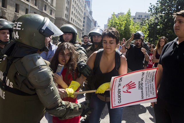 Pro and anti-abortion demonstrators clash, in front of a police officer in riot gear, during a pro-abortion protest in Santiago, Chile, Monday, March 21, 2016. The protest took place as another much larger protest was taking place in front of the government palace. The recent decriminalization of abortion by the national congress in cases or rape, or if the mother's life is in danger, or if the fetus is not viable, has prompted demonstrations by groups in favor and against abortion. (AP Photo/Esteban Felix)