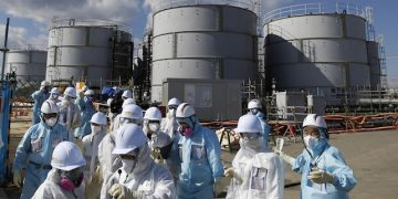 Members of a media tour group wearing a protective suit and a mask walk together after they receive a briefing from Tokyo Electric Power Co. (TEPCO) employees (in blue) in front of storage tanks for radioactive water at the tsunami-crippled Fukushima Dai-ichi nuclear power plant in Okuma, Fukushima Prefecture, northeastern Japan, Wednesday, Feb. 10, 2016. In one month, Japan is marking the fifth anniversary of a devastating earthquake and tsunami that hit on March 11, 2011 and left nearly 19,000 people dead or missing, turned coastal communities into wasteland and triggered a nuclear crisis. (Toru Hanai/Pool Photo via AP)