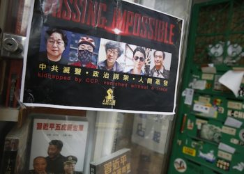 A poster featuring five missing Hong Kong booksellers is displayed by their supporters at the entrance of the closed Causeway Bay Bookstore which is known for gossipy titles about Chinese political scandals and other sensitive issues that are popular with visiting tourists from the mainland in Hong Kong, Friday, Feb. 5, 2016. Mainland Chinese authorities say they're investigating three missing Hong Kong booksellers for unspecified criminal activity, shedding more light on a case that's gripped residents with fear that Beijing is tightening its hold on the city. (AP Photo/Kin Cheung)