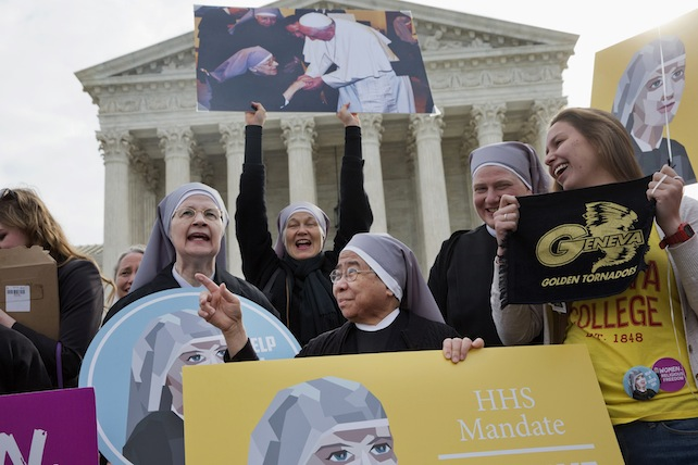 Nuns with the Little Sisters of The Poor, including Sister Celestine, left, and Sister Jeanne Veronique, center, rally outside the Supreme Court in Washington, Wednesday, March 23, 2016, as the court hears arguments to allow birth control in healthcare plans in the Zubik vs. Burwell case. (AP Photo/Jacquelyn Martin)