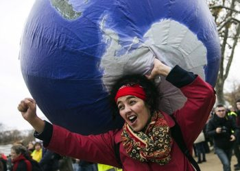 epa05066314 A woman carries an inflatable earth as thousands of people demonstrate in front of the Eiffel Tower for climate change in Paris, France, 12 December 2015. The 21st Conference of the Parties (COP21) is held in Paris from 30 November to 11 December aimed at reaching an international agreement to limit greenhouse gas emissions and curtail climate change.  EPA/ETIENNE LAURENT