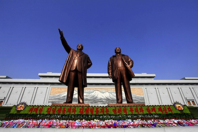 """Flowers are laid under bronze statues of North Korea's late leaders Kim Il Sung, left, and Kim Jong Il at Mansu Hill in Pyongyang, North Korea, Friday, April 15, 2016, to commemorate North founder Kim Il Sung's birthday. The banner reads: """"Great comrades Kim Il Sung and Kim Jong Il are with us eternally."""" (AP Photo/Kim Gwang Hyon)"""