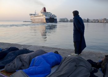 Migrants and refugees sleep as a man from Pakistan covered with a blanket looks on a ferryboat leaving the port of the Greek island of Chios, Wednesday, April 6, 2016.Volunteers are concerned about children health of some 300 migrants and refugees that manage to leave the VIAL detention center a few days ago. Authorities said that more than 1700 migrants and refugees are in the island. (AP Photo/Petros Giannakouris)