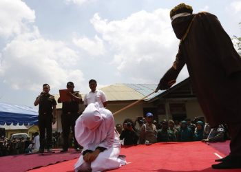 epa05188205 An Acehnese woman is whipped in front of the public at Rukoh Village, Banda Aceh, Indonesia, 01 March 2016. Eighteen Acehnese got whipped for violating the sharia law, including for gambling, drinking alcohol and for dating between a man and a woman. Whipping punishment is one form of punishment imposed in Aceh for violating the application of Islamic Shari'a.  EPA/HOTLI SIMANJUNTAK