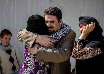 In this Thursday, March 31, 2016 photo, Balkis, 15, embraces her father, Sheikh Matar, after being separated from him for over a year. Balkis stayed with her mother, younger sister, and two younger brothers in Islamic State group controlled territory after her father was forced to flee to the Kurdish north. They were able to come together when recent fighting between Iraqi forces and IS created an opportunity for them to escape late the previous night. (AP Photo/Cengiz Yar)