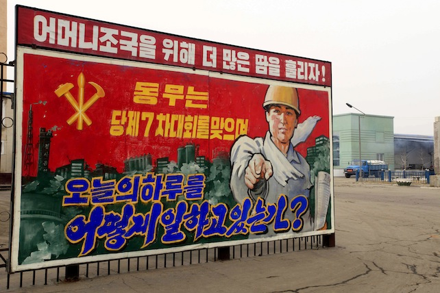 """In this Sunday, March 13, 2016 photo, a truck loaded with bags of fertilizer leaves the Hungnam Fertilizer Complex behind a propaganda billboard that reads: """"How are you spending today on the occasion of the party's 7th conference?"""" in Hungnam, South Hamgyong Province, North Korea. North Koreans are being mobilized en masse to boost production and demonstrate their loyalty to leader Kim Jong Un in a 70-day campaign aimed at wiping out """"indolence and slackness."""" Bright red flags and propaganda posters have gone up around the country to emphasize the importance of meeting or exceeding production targets. (AP Photo/Kim Kwang Hyon)"""