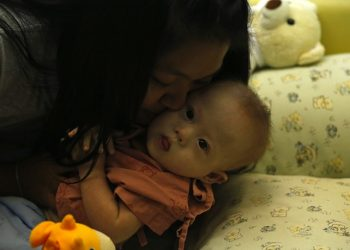 epa04340353 A Thai surrogate mother, Pattharamon Janbua, 21, kisses her seven-month-old Down's Syndrome baby, Gammy or Naruebet Mincharoen at a hospital in Chonburi province, Thailand, 04 August 2014. The Australian father of a baby with Down's syndrome born to a surrogate in Thailand has denied abandoning the child while taking home his healthy twin sister. Gammy is one of twins born to Thai woman Pattharamon Janbua who said she was paid by the unidentified Australian couple to deliver an in vitro fertilized baby. The case sparked a public outcry and put a spotlight on transnational commercial surrogacy laws in Thailand and Australia.  EPA/RUNGROJ YONGRIT