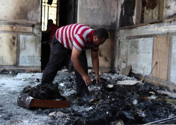 epa03825673 An Egyptian man cleans the floor from charred objects inside the Prince Tadros church which was set to fire overnight in Minya, about 245 kilometers south of Cairo, Egypt, 15 August 2013. Egyptian government has said that 522 people were killed in the country on 14 August in violence linked to the police's break-up of major protest camps by Islamists in Cairo. Spokesman Mohammed Fatallah said that the figure included 289 killed in the crackdown on the two pro-Morsi protest vigils in the north-east and south of the capital.  EPA/GIRO MAIS