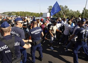 epa04912900 Police defines the way of the migrants walking - one with an EU flag - on the Budaorsi Street, in Budapest,  Migrants walk along Budaorsi Street on their way out of Budapest, Hungary, 04 September 2015. Several thousand migrants left the Keleti station this afternoon heading for Germany on foot. Hundreds of migrants on 03 September rushed the platforms in Budapest after Hungarian police opened the city's Keleti station, which had been blocked to migrants since 01 September. Hungary's railway service said there were no trains headed to Western Europe for the time being. Thousands of refugees - many of whom have traveled from Africa and the Middle East in the hopes of reaching countries like Germany and Sweden - have been stranded at the station.  EPA/ZSOLT SZIGETVARY HUNGARY OUT