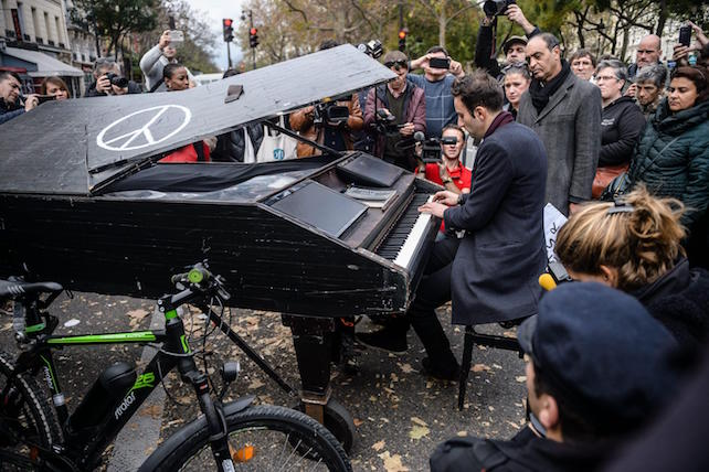 epa05028435 Pianist Davide Martello plays the  Lennon's song Imagine in front of the memorial set near the Bataclan concert venue in Paris, France, 16 November 2015. More than 130 people were killed and hundreds injured in the terror attacks which targeted the Bataclan concert hall, the Stade de France national sports stadium, and several restaurants and bars in the French capital on 13 November. Authorities believe that three coordinated teams of terrorists armed with rifles and explosive vests carried out the attacks, which the Islamic State (IS) extremist group has claimed responsibility for.  EPA/CHRISTOPHE PETIT TESSON