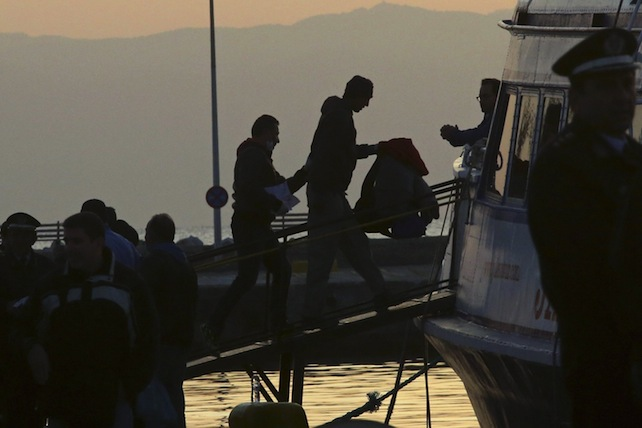 epa05243045 A migrant is escorted by a Frontex officer into a ferry in the port of Mytilene, Lesvos island, Greece, 04 April 2016. Some 160 migrants, from Pakistan, Bangladesh and Morroco, who refused to apply for asylum, have been deported on 04 April early morning to Turkey, after the agreement between European Union (EU) and Turkey on the refugees crisis.  EPA/ORESTIS PANAGIOTOU