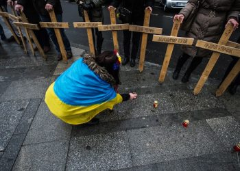epa04632046 A woman covered by Ukraine flag lights candles as people hold wooden crosses commemorating the people who died during the protests on Kiev's Independent Square, in Prague, Czech Republic, 22 February 2015. Ukraine marked the first year anniversary of the escalated violence in Maidan where it resulted in at least 100 people being killed.  EPA/FILIP SINGER