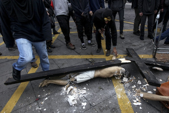 A crucified Christ lies on a street destroyed after a group of hooded vandals carried it out of a church that they looted in the Chilean capital in Santiago, Chile, Thursday, June 9, 2016.(AP Photo/Felix Marquez)