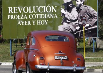 epa05251510 A vehicle drives past a billboard with an image of former Cuban President Fidel Castro (R) and Cuban revolutionary Camilo Cienfuegos (2-R), and a message reading 'Revolution, Daily Feat Yesterday and Today', in Havana, Cuba, 09 April 2016. The ruling Communist Party is preparing for its 7th Congress on 16-19 April.  EPA/Ernesto Mastrascusa