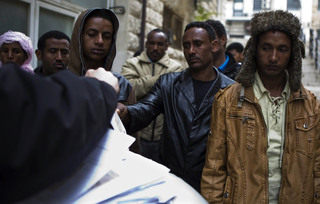 epa03588714 A group of Eritrean and Sudanese migrants wait to receive a temporary permit from an official, granting them permission to remain in Israel for the next four months, in Jerusalem, Israel, 17 Febraury 2013. The UN has claimed that Israel is coercing Eritrean refugees into signing 'voluntary' departure forms to return to Eritrea - where the UN says their lives would be in danger - or be sent to another country, a claim which Israel denies. Eritreans comprise some 60% of African migrants that have crossed into Israel. Up until June 2012, Eritrean and North Sudanese migrants who entered Israel illegally were released from prison after initially being detained at the border. The law has since been amended, giving the Israeli authorities the capacity to jail illegal African migrants and refugees for three years or more. The completion of the border fence with Egypt has also contributed to restricting the numbers of migrants attempting to cross into Israel.  EPA/JIM HOLLANDER