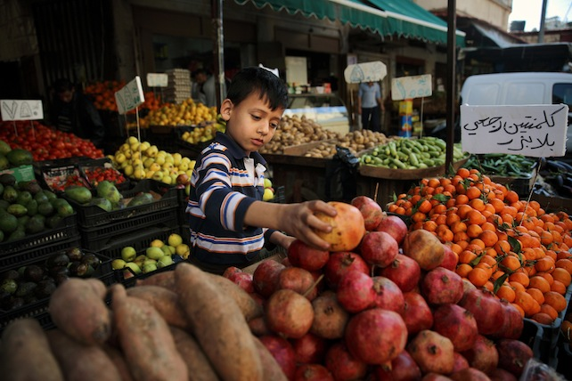 In this Friday, Feb. 19, 2016 photo, Syrian refugee Mohammed Hassan, 8, who fled with his family from Idlib, Syria, rearranges fruits on display for sale at a market in the Palestinian refugee camp of Sabra in Beirut, Lebanon. The U.N.'s children agency, UNICEF, says there are 2.8 million children out of school in the region, and child refugees are particularly at risk of exploitation and abuse, with large numbers being left with no choice but to go out to work, rather than attend school. (AP Photo/Bilal Hussein)