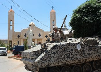 A Lebanese army soldier from the special forces unit stands on a APC during a patrol in front a church in Qaa, a predominantly Lebanese Christian village near the Syrian border were suicide bombers blow themselves among civilians on Monday, eastern Lebanon, Tuesday, June 28, 2016. Lebanese troops detained 103 Syrians for illegal entry into the country, in a security sweep on Tuesday, a day after a series of deadly bombings struck a village near the border with Syria, the military said. The unprecedented attacks nine explosions in all, eight of them suicide bombings triggered fear and panic among residents of Qaa village and a deepening sense of foreboding in Lebanon, which has grappled for over five years with spillovers from neighboring Syria's civil war. (AP Photo)