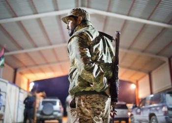 FILE - In this Wednesday, Feb. 18, 2015 file photo, a Libyan military soldier stands guard at the entrance of a town, 110 kilometers (68 miles) from Sirte, Libya. From east and west, the forces of Libya's rival powers are each moving on the city of Sirte, vowing to free it from the hold of the Islamic State group. The danger is they could very well fight each other as well. Rather than becoming a unifying cause as the United States and Europe have hoped, the fight against the jihadi group threatens to cause greater fragmentation in Libya, which has been torn apart among rival militias, tribes, governments and parliaments since the 2011 downfall of longtime autocratic ruler Moammar Gadhafi in a NATO-backed rebellion. (AP Photo/Mohamed Ben Khalifa, File)