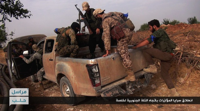 """This image posted on the Twitter page of Syria's al-Qaida-linked Nusra Front on Wednesday, June 15, 2016, which is consistent with AP reporting, shows Nusra Front fighters on their vehicle preparing to leave and battle against Syrian troops and pro-government gunmen, at the hilltop of Khalsa village, southern Aleppo, Syria. Activists reported intense fighting between government troops and rebels in southern Aleppo where the insurgent groups are angling for a strategic hill to expand their presence in the area. The Britain-based Syrian Observatory for Human Rights said the government repelled a rebel advance in the area amid intense air raids. Arabic, bottom right, reads, """"departure of the support units to the southern hill of Khalsa."""" (Al-Nusra Front Twitter page via AP)"""