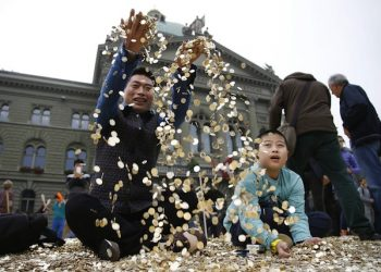 epa03895861 Chinese tourists from Shanghai play in a pile of coins after activists dumped a truck load of 8 Million five-centime coins - representing one coin for every person living in Switzerland - at the Federal Square in front of the parliament building in Bern, Switzerland, 04 October 2013. The about 15 tons of money are worth 400,000 Swiss Francs. At the same time the required signatures for the ''National Initiative for a Unconditional Basic Income' were delivered to the Swiss government.  EPA/PETER KLAUNZER