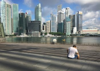 A man talks on his mobile phone while in the background, the Marina Bay financial district of Singapore is seen on Tuesday, July 5, 2016. Singapore which is about the size of New York City, has a population of more than 5 million and its economy relies mainly on finance, tourism and manufacturing. (AP Photo/Wong Maye-E)