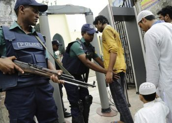 epa05425758 Security officials stand guard in front of the entrance of the National mosque and check people through archway metal detector during the Friday prayer in Dhaka 15 July 2016. Security has been beeped up after the terror attacks in Gulshan that left 20 hostages dead on 01 July and in another attack during the Eid prayer that killed four including two policemen in Sholakia, Kishoregonj on 07 July 2016.  EPA/ABIR ABDULLAH