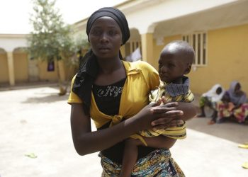 Binta Ibrahim, holds an unidentified child after she described how she trekked for two days from Nbitha to Boko Haram's hideout in the Sambisa Forest with 2-year-old Matthew and 4-year-old Elija Yohanna strapped to her back and 4-year-old Maryam Samaila clinging to her waist following her rescued by Nigerian soldiers from Sambisa Forest , at a refugee camp in Yola, Nigeria Monday, May 4, 2015. Even with the crackle of gunfire signaling rescuers were near, the horrors did not end: Boko Haram fighters stoned captives to death, some girls and women were crushed by an armored car and three died when a land mine exploded as they walked to freedom. (ANSA/AP Photo/Sunday Alamba)