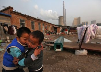 epa03017683 Chinese boys play in the courtyard of their home beside a power plant  in Beijing, China, 28 November 2011. Reports state that China, the world's largest emitter of greenhouse gases, is rallying key allies to push developed nations to agree to binding targets for reducing carbon emissions ahead of climate change talks in Durban even as it maintains that developing countries continue to be exempt as these would hamper efforts to alleviate poverty.  EPA/HOW HWEE YOUNG