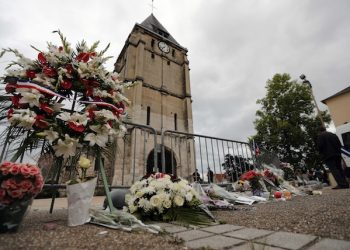 A wreath of flowers from Muslim of France Associations is placed with flowers next to the church where an hostage taking left a priest dead the day before in Saint-Etienne-du-Rouvray, Normandy, France, Wednesday, July 27, 2016. The Islamic State group crossed a new threshold Tuesday in its war against the West, as two of its followers targeted a church in Normandy, slitting the throat of an elderly priest celebrating Mass and using hostages as human shields before being shot by police. (AP Photo/Francois Mori)
