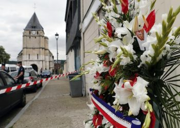 A wreath of flowers from the Muslims of France Association is placed outside the church where a hostage taking left a priest dead the day before, in Saint-Etienne-du-Rouvray, Normandy, France, Wednesday, July 27, 2016. The Islamic State group crossed a new threshold Tuesday in its war against the West, as two of its followers targeted a church in Normandy, slitting the throat of an elderly priest celebrating Mass and using hostages as human shields before being shot by police. (AP Photo/Francois Mori)