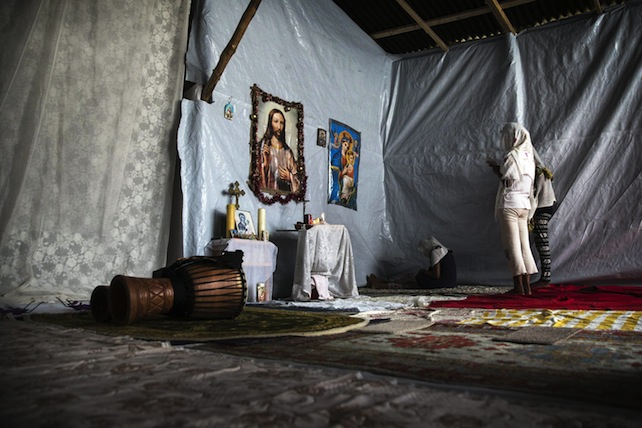 epa04875965 Three migrant women from Eritrea pray in a small church they have built at the makeshift migrant camp the 'Jungle' on the outskirts of Calais, France, 07 August 2015. More than 3,000 migrants live in the camp according to associations and non-governmental organizations (NGOs).  EPA/ETIENNE LAURENT