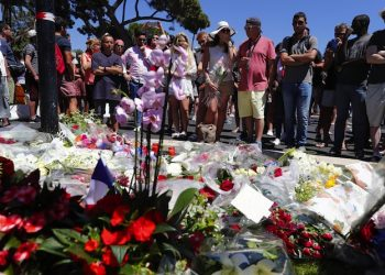epa05426108 People gather in front of the memorial set on the 'Promenade des Anglais' where the truck crashed into the crowd during the Bastille Day celebrations, in Nice, France, 15 July 2016. According to reports, at least 84 people died and many were wounded after a truck drove into the crowd on the famous Promenade des Anglais during celebrations of Bastille Day in Nice, late 14 July. Anti-terrorism police took over the investigation in the incident, media added.  EPA/IAN LANGSDON