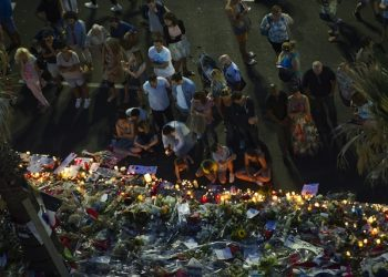 epa05429790 People gather at a makeshift memorial of flowers and candles on the 'Promenade des Anglais' where the truck crashed into the crowd during the Bastille Day celebrations, in Nice, France, 17 July 2016. According to reports, at least 84 people died and many were wounded after a truck drove into the crowd on the famous Promenade des Anglais during celebrations of Bastille Day in Nice, late 14 July.  EPA/OLIVIER ANRIGO