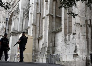 French police officers stand guard during a mass in tribute to priest Jacques Hamel who was killed by two attackers at the Saint Etienne church,  outside the Cathedral Notre Dame in Rouen, Normandy, France, Wednesday, July 27, 2016. The Islamic State group crossed a new threshold Tuesday in its war against the West, as two of its followers targeted a church in Normandy, slitting the throat of an elderly priest celebrating Mass and using hostages as human shields before being shot by police. (AP Photo/Francois Mori)