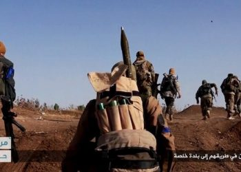 """FILE - This file image posted on the Twitter page of Syria's al-Qaida-linked Nusra Front on Tuesday, June 14, 2016, which is consistent with AP reporting, shows Nusra Front fighters moving forward to fight against Syrian troops and pro-government gunmen at the hilltop of Khalsa village, southern Aleppo, Syria. Al-Qaida's branch in Syria is considering splitting ties with the global terror group, but the Nusra Front's intention to make it more appealing to the West may in fact be a tactical move aimed at undermining ongoing talks between the U.S. and Russia on a military partnership in Syria. Arabic, bottom right, reads, """"Jihadis on their way to Khalsa village."""" (Al-Nusra Front Twitter page via AP, File)"""
