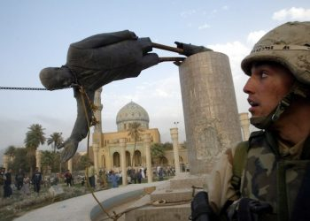 A U.S. soldier watches as a statue of Iraq's President Saddam Hussein falls in central Baghdad April 9, 2003. U.S. troops pulled down a 20-foot (six metre) high statue of President Saddam Hussein in central Baghdad on Wednesday and Iraqis danced on it in contempt for the man who ruled them with an iron grip for 24 years. In scenes reminiscent of the fall of the Berlin Wall in 1989, Iraqis earlier took a sledgehammer to the marble plinth under the statue of Saddam. Youths had placed a noose around the statue's neck and attached the rope to a U.S. armoured recovery vehicle.      REUTERS/Goran Tomasevic