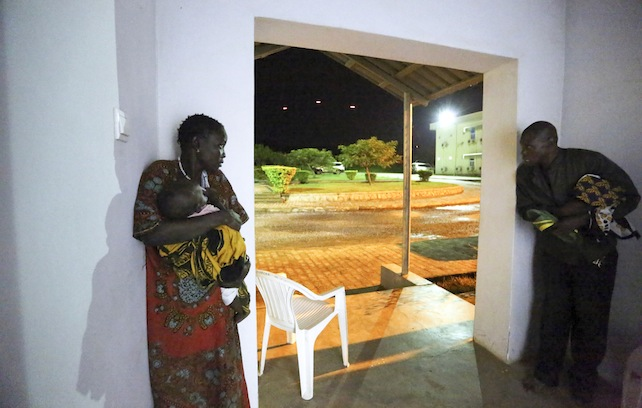 In this photo taken late Friday, July 8, 2016 and released by the United Nations Mission in South Sudan (UNMISS),  taking cover in the doorway of the UN offices as the fighting kicks off, tracers flying by in the background, the fighting was directly on the perimeter of the UN base the UN compound in the capital Juba, South Sudan. The president of South Sudan and his opposition rival both called Monday for a cease-fire in a conflict that has seen fierce clashes between their forces spread from the capital to a southeastern town. (Eric Kanalstein/UNMISS via AP)