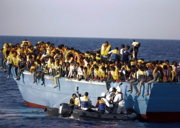 Italian officers rescue a woman from a crowded wooden boat carrying more than seven hundred migrants, during a rescue operation in the Mediterranean sea, about 13 miles north of Sabratha, Libya, Monday, Aug. 29, 2016. Thousands of migrants and refugees were rescued Monday morning from more than 20 boats by members of Proactiva Open Arms NGO and Italian military officers. (AP Photo/Emilio Morenatti)
