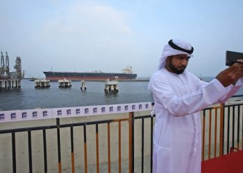 An Emirati official takes selfie as an oil tanker approaches to the new Jetty during the launch of the new $650 million oil facility in Fujairah, United Arab Emirates, Wednesday, Sept. 21, 2016. The United Arab Emirates has opened its first jetty outside the Persian Gulf that is capable of loading oil onto some of the world's biggest tanker ships. (AP Photo/Kamran Jebreili)