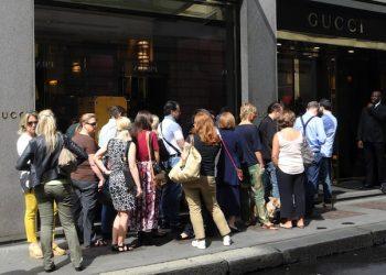 Alcune persone in coda per entrare nella boutique Gucci in via Montenapoleone a Milano, 5 luglio 2014, prima giornata di saldi. ANSA / MATTEO BAZZI