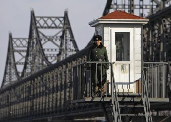 epa03651696 A Chinese soldier stand guard at a guard post beside the Sino-Korean Friendship Bridge connecting Sinuiju, North Korea, along the Yalu River in the Chinese city of Dandong, Liaoning Province, China, 06 April 2013. North Korean leader Kim Jong-un has ordered the country's military to increase artillery production, a televised report out of Pyongyang showed 06 April.  EPA/HOW HWEE YOUNG