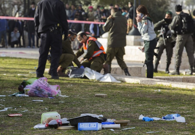 Israeli police and army personnel go through the belongings (in foreground) of Israeli soldiers near to the truck (L, but unseen) that rammed into a group of army soldiers killing in Jerusalem, 08 January 2017. Four Israeli soldiers were killed and another 15 wounded in the attack carried out by a Palestinian who had been released from Israeli jail. The driver of the truck, reported by local media to be an Arab Israeli from East Jerusalem, was shot and killed by security forces, media reports said.  ANSA/JIM HOLLANDER