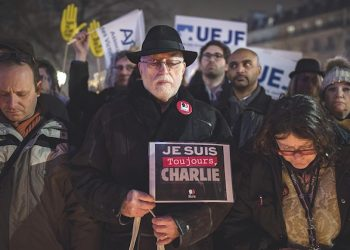 epa05703941 A man hols a placard reading, 'I am Charlie', as Parisians light candles to mark the two-year anniversary of the Charlie Hebdo attack, at the monument on Place de la Republique in Paris, France, 07 January 2017. France this week commemorates the victims of the 2015 Islamist militant attacks on satirical weekly Charlie Hebdo and a Jewish supermarket.  EPA/IAN LANGSDON