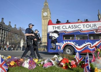 epa05868002 Armed police walk past flowers in the  Parliament Square near to the scene of 22 March terror attack in central London, Britain, 24 March 2017. Scotland Yard said on 24 March 2017 that police have made nine arrests in relation to the terror attack in the Westminster Palace grounds and on Westminster Bridge on 22 March 2017 leaving at least five people dead, including the attacker, and 29 people injured.  EPA/HANNAH MCKAY